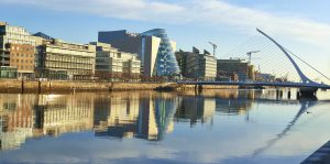 Modern buildings on Liffey river in Dublin and Harp bridge